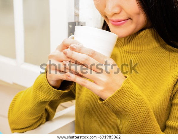 Young beautiful girl holding a white cup, drinking a hot drink