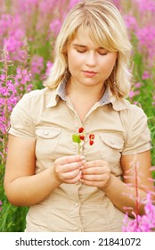 The young beautiful girl holds in hands wild strawberry against high pink florets.