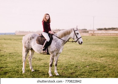 Young beautiful girl is horse riding in the field