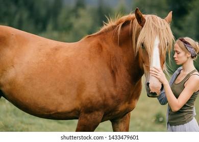 Young beautiful girl hugs horse at nature.