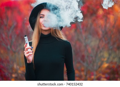 Young beautiful girl inblack hat vaping vape device with cloud of vape outdoors in autumn.