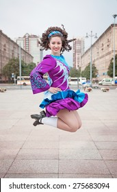 Young beautiful girl in irish dance dress and wig jumping outdoor
