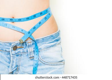 Young beautiful girl in jeans short measures her body parts