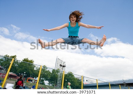 young, beautiful girl is jumping under the sky