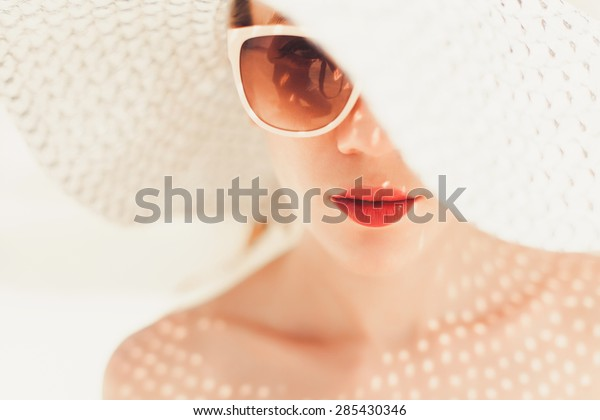 大きな帽子をかぶった若い美しい女の子と赤い唇を持つサングラスがビーチにポーズをとっている