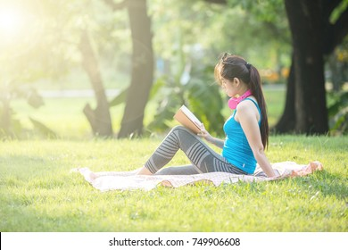Young beautiful girl laying on the grass in park reading a book with her headphones