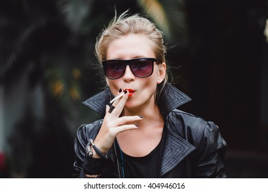 young beautiful girl in a leather jacket blonde with red lips Smoking a cigarette on the street produces smoke, fashion woman, red lips