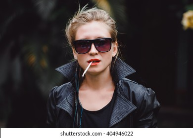 young beautiful girl in a leather jacket blonde with red lips Smoking a cigarette on the street produces smoke, pretty woman,
