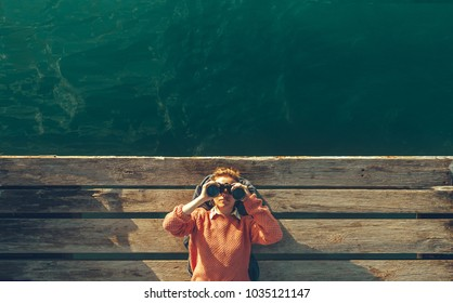 Young Beautiful Girl Lies On A Pier Near The Sea And Looks Through Binoculars On Tje Sky. Travel Search Journey Concept