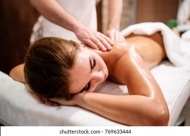Young beautiful girl lies on a massage procedure in Spa salon close up