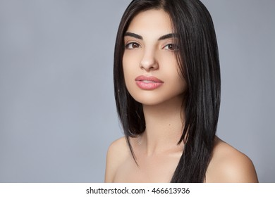 Young beautiful girl with long black hair. Tanned and clear skin. Hair straight and healthy.