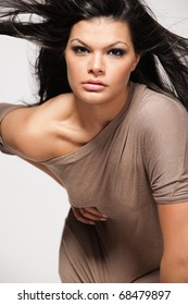 Young beautiful girl with long black hair in gray dress.