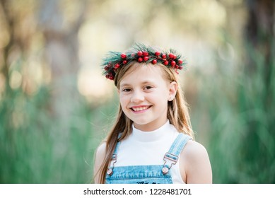 Young beautiful girl with long brown hair celebrating an Australian summer Christmas wearing holly berry wreath flower crown denim overalls  smiling outdoors