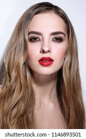 Young beautiful girl with long curly hair and red lipstick