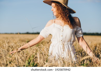 Young beautiful girl with long curly hair poses in a wheat field in the summer at sunset. The girl in the hat. Toning.