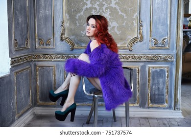 The young beautiful girl with long curly red hair sits on a chair, a violet fur coat and black underwear, a footwear on a high heel, long legs, a sexual figure, flirts, a languishing look, ginger hair