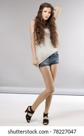 young beautiful girl with long curly hair wearing mini short jeans and posing