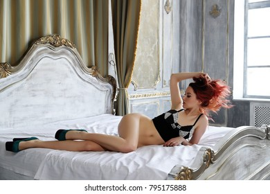 The young beautiful girl with long curly red hair in a violet fur coat and black underwear and in footwear on a high heel poses, long legs, a sexual figure, flirts, a languishing look, ginger hair