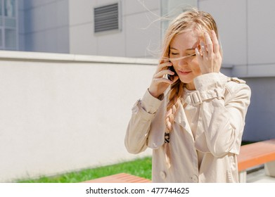 young beautiful girl with long hair fanned by the wind, wearing a raincoat, talking on cell phone on the street. telephone communication, liaison, pleasant conversation about the business