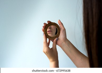 young beautiful girl looking in the mirror in the white background