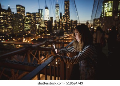 Young beautiful girl looking at mobile phone at Brooklyn Bridge at night. Amazing view of New York on the background.