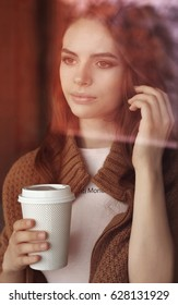 Young beautiful girl looking in the window holding a glass of fresh coffee, thoughtful look