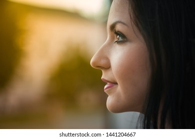 Young beautiful girl looks in profile, close-up. Profile portrait of a beautiful young woman looking at a warm pagoda from the window. Close up on the face, the joy of the solar pagoda.