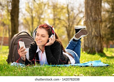 Young beautiful girl lying on a blanket on the grass in the park, listening to music and looking at the phone.