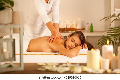 Young beautiful girl lying on massage table and enjoying massage.