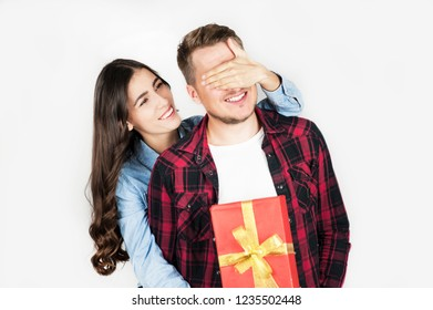 A young beautiful girl makes a surprise to her boyfriend and gives him a gift by covering his eyes with a hand. They laugh emotionally.