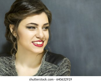 Young beautiful girl with makeup. Portrait on a blue background with copy space