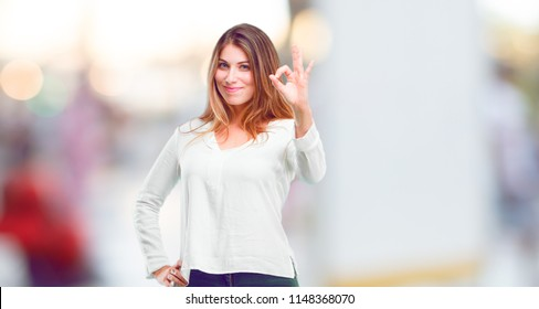 "young beautiful girl making an ""alright"" or ""okay"" gesture approvingly with hand, looking happy and satisfied. Positive check sign."