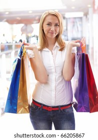 Young beautiful girl in the mall with shopping bags. Symbol of shopping.