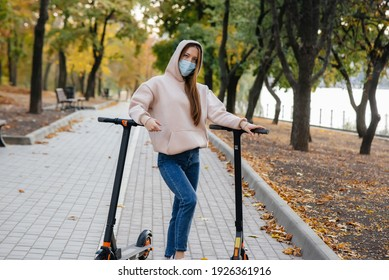 A young beautiful girl in a mask is riding in the Park on an electric scooter on a warm autumn day. Walk in the Park.