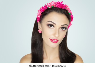 Young beautiful girl, massive accessory flowers crown wreath. Big eyes dreamy opened. Professional make-up bright shiny glitters shadows pencil technique smoky eyes, good shape eyebrows matte lipstick