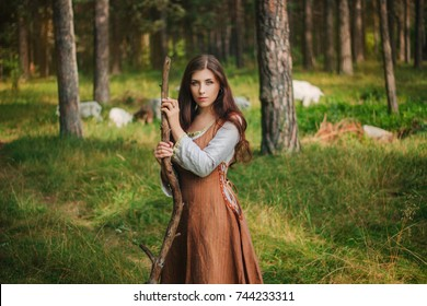Young beautiful girl in medieval cowboy clothes, with a stick in hand. Barefoot on the ground. Against the background of the forest and green grass. A model with clean skin.