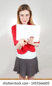 Young beautiful girl in mini skirt holding empty white paper and showing something with index finger