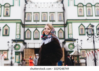 A young beautiful girl in a mink coat and a Russian folk scarf walks around the Izmailovo Kremlin. Moscow, Russia.