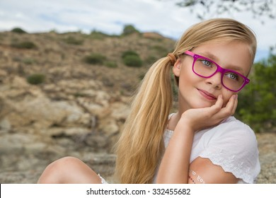 Young beautiful girl model long curly blond hair smiling in pink glasses and a chic dress at the pool with railing and rocks and the sea in Spain, Greece, Santorini