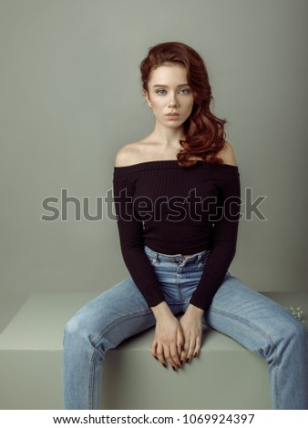 b6b3535b Young beautiful girl model, sitting on cube, dressed in blue jeans and a  black sweater on a gray background - Image