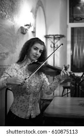 Young beautiful girl musician violinist playing the violin