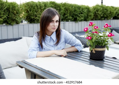 Young beautiful girl in the office clothes waiting for a cup of coffee in a cafe