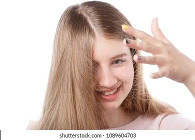 young beautiful girl on an isolated white background looks at an electrified hair that are stuck to her hand.