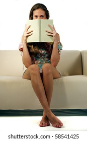 young beautiful girl on a sofa holding a book to her face