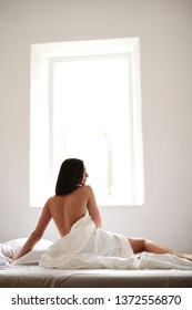 young beautiful girl on a white bed against the window