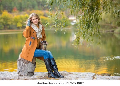 Young beautiful girl in an orange coat. The blonde is holding a flashlight with a candle. Rest at the lake
