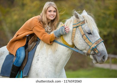 Young beautiful girl in an orange coat is sitting on a white horse. A girl is hugging a horse. Horseback riding