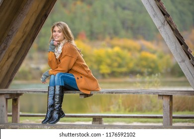 Young beautiful girl in orange coat and high boots. The model sits on a wooden bench. Spring or autumn nature