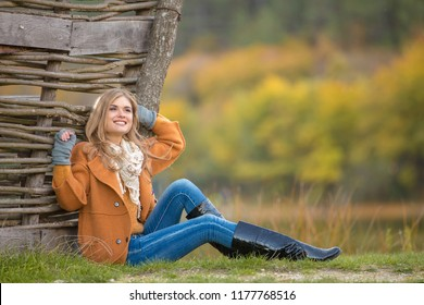 Young beautiful girl in orange coat and high boots. The model sits near the wicker fence. Spring or autumn weather