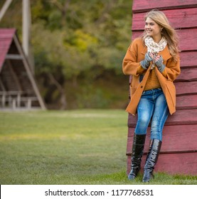 Young beautiful girl in orange coat and high boots. The model stands on the background of a red wooden wall. Spring or autumn weather